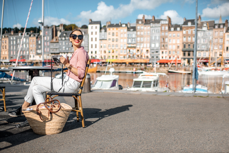 Young woman enjoying coffee sitting at the cafe outdoors near the harbour with beautiful buildings on the background in Honfleur old town, France
