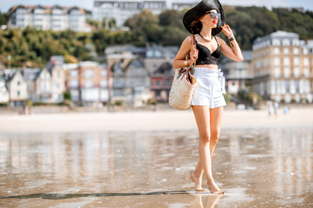 Beautiful woman walking on the beach with great view on the luxury houses in Trouville resort, France