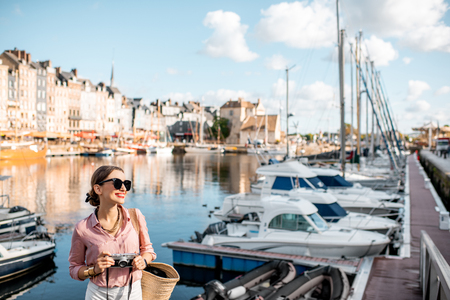 Young woman tourist enjoying beautiful view on the harbour traveling in Honfleur town in Normandy, France 写真素材