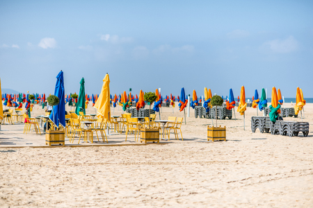 Famous beach with colorful umbrellas in Deauville town in France
