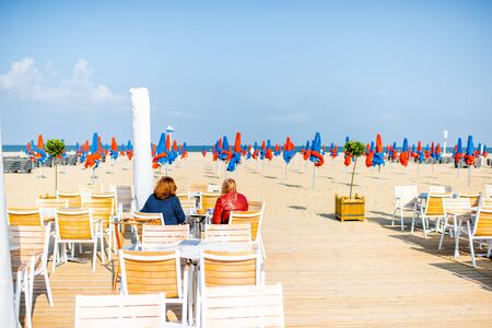 DEAUVILLE, FRANCE - September 06, 2017: View on the cafe terrace with yellow chairs and people have a rest on the beach in Deauville