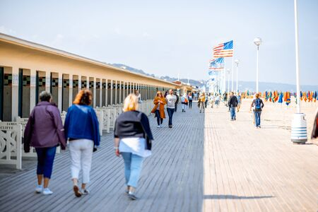 DEAUVILLE, FRANCE - September 06, 2017: Planches promenade with people walking near the locker rooms of the famous fiilm actors in Deauville
