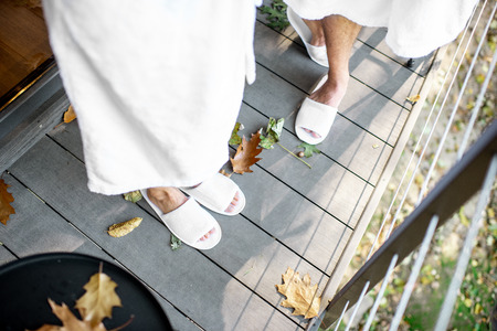 Couple in bath robe and slipppers standing on the terrace with beautiful leaves outdoors. View from above with no face Stock Photo