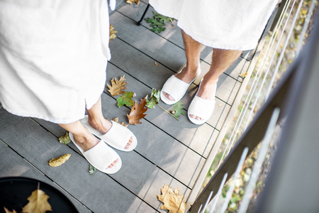 Couple in bath robe and slipppers standing on the terrace with beautiful leaves outdoors. View from above with no face 免版税图像