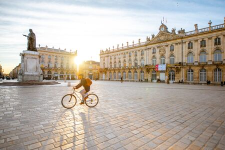 NANCY, FRANCE - September 10, 2017: Morning view on Stanislas square with monument and man ride a bicycle at the old town of Nancy city, France