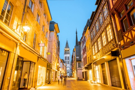 Street view with illuminated buildings and famous cathedral during the twilight in the old town of Rouen city in France