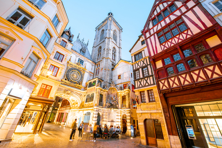 Street view with illuminated buildings and famous clock tower during the twilight in the old town of Rouen city in France