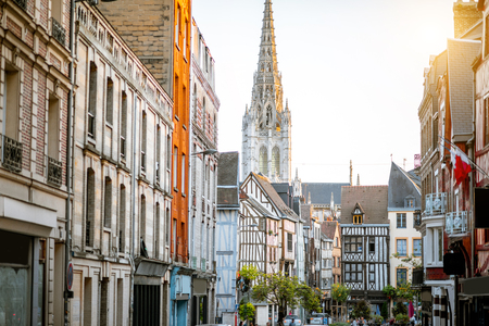 Street view with beautiful old buildings and cathedral tower on the background in Rouen city, the capital of Normandy region in France