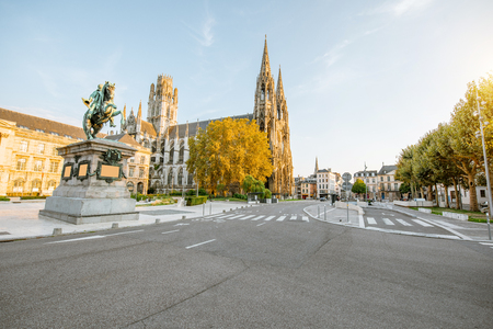 Street view with Napoleon monument and church of saint-Ouen during the sunset in Rouen city, France