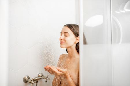 Mujer joven y hermosa lavándose la cara, tomando una ducha en la cabina blanca