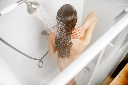Woman washing her beautiful long hair, while taking a shower standing back in the shower cabin. View from above Stockfoto