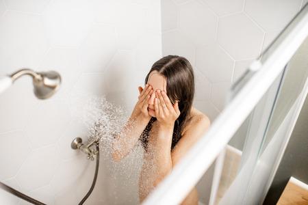 Mujer joven y hermosa lavándose la cara, tomando una ducha en la cabina blanca. Vista desde arriba