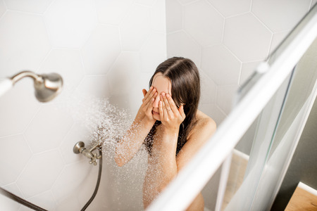 Young and beautiful woman washing her face, taking a shower in the white cabin. View from above Imagens - 113338010