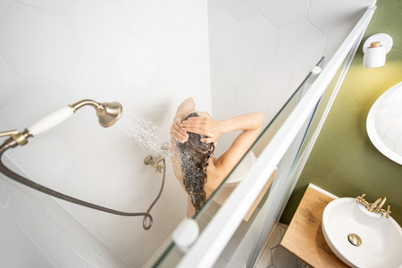 Woman washing her beautiful long hair, while taking a shower standing back in the shower cabin. View from above Standard-Bild
