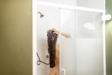 Woman washing her beautiful long hair, while taking a shower standing back in the shower cabin. Wide view with copy space on the wall
