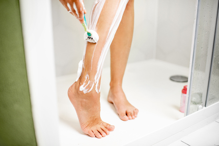 Woman shaving her legs with razor and foam in the shower cabin Stockfoto