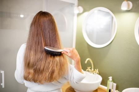 Frau im Bademantel, die Haare mit Bürste im Badezimmer kämmt, Rückansicht