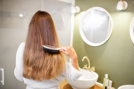 Woman in bathrobe combing hair with brush in the bathroom, rear view