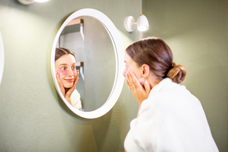 Young woman in bathrobe taking care of herself looking into the mirror with patches under eyes in the bathroom