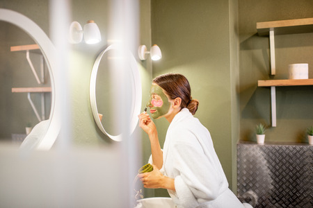 Young woman in bathrobe applying green mask on her face looking into the mirror in the modern green bathroom