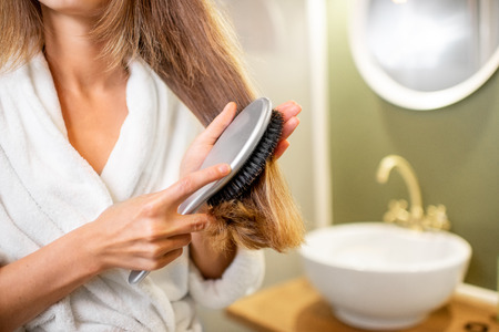 Woman combing hair with brush in the bathroom, close-up view with no face