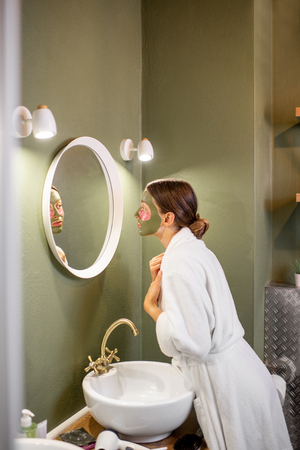 Woman in bathrobe taking care of herself with facial mask looking into the mirror in the beautiful green bathroom