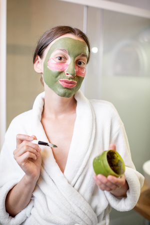 Portrait of a young woman in bathrobe with facial green mask and patches under her eyes in the bathroom