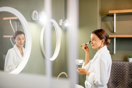 Young woman in bathrobe applying powder with brush looking into the round mirror in the bathroom