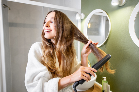 Young and happy woman in bathrobe straightening hair with straightener in the bathroom