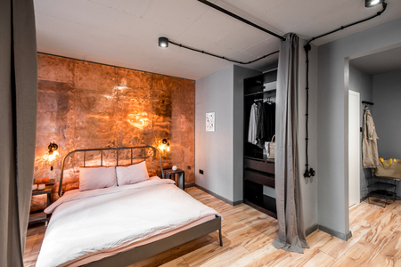 Modern loft bedroom interior with wall made of copper metal. Real photography