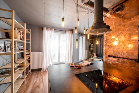 Moderna sala de cocina tipo loft realizada en colores rosa y gris con pared de cobre Foto de archivo