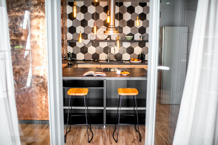 Loft kitchen interior with hexagonal black and white tiles and copper wall 스톡 콘텐츠 - 113339357