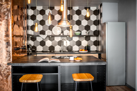 Loft kitchen interior with hexagonal black and white tiles and copper wall