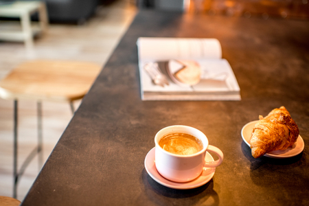 Coffee with croissant and magazine on the kitchen table at the modern loft interior