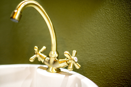 Retro style bathtub faucet made in bronze on the green wall backround
