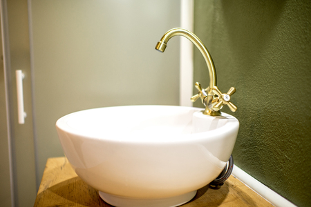 Round sink with retro tap on the green wall background in the bathroom Banco de Imagens