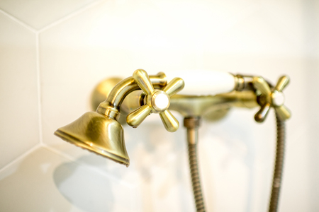 Retro style bathtub faucet made in bronze on the white tiles background, close-up view Stock Photo - 113339425