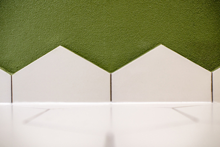Close-up of the floor corner made with hexagonal white tiles and green walll
