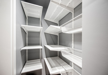 Empty wardrobe room with white metal shelves in the apartment
