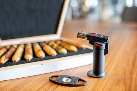 Close-up of luxury cigar set with lighter on the wooden table indoors