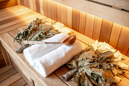 Bath brooms with towels and scoop on the bench at the russian traditional sauna Stok Fotoğraf