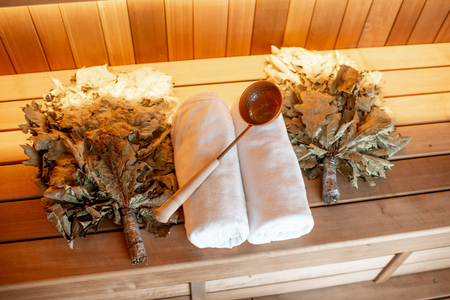 Bath brooms with towels and scoop on the bench at the russian traditional sauna 写真素材