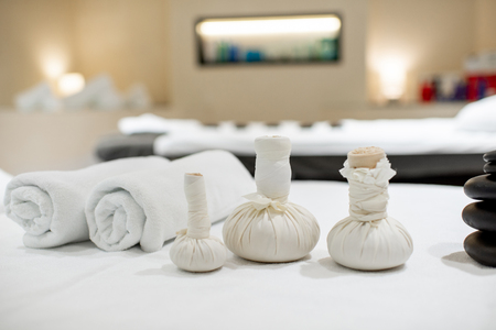 Herbal bags with stones for massage on the white towel indoors Stock Photo