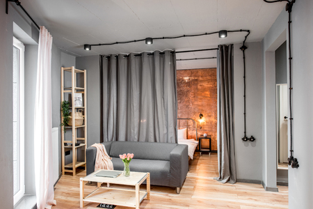 Modern living room in loft style made in grey colors with sofa and bedroom behind the curtains Imagens