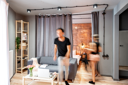 Modern living room interior with motion blurred couple doing their housework 写真素材
