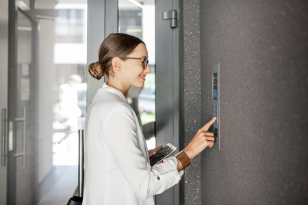 Young business woman in white suit entering code on the intercom keyboard of the residential modern building Archivio Fotografico
