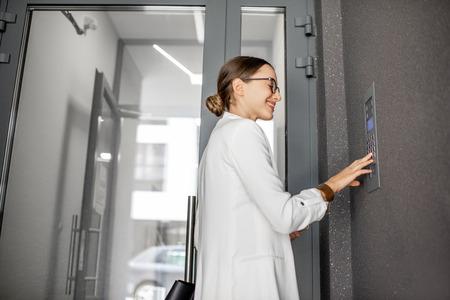 Jonge zakenvrouw in wit pak die code invoert op het intercomtoetsenbord van het moderne woongebouw