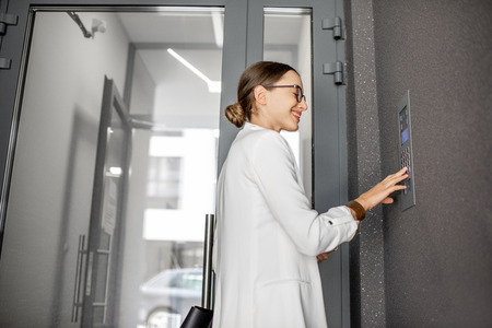 Young business woman in white suit entering code on the intercom keyboard of the residential modern building Stockfoto