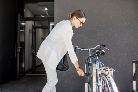 Young business woman in white suit opening bicyle lock near the modern residential building entrance 版權商用圖片