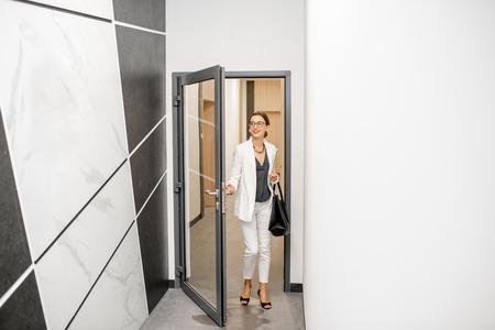 Donna d'affari in abito bianco che cammina nel corridoio del moderno edificio residenziale